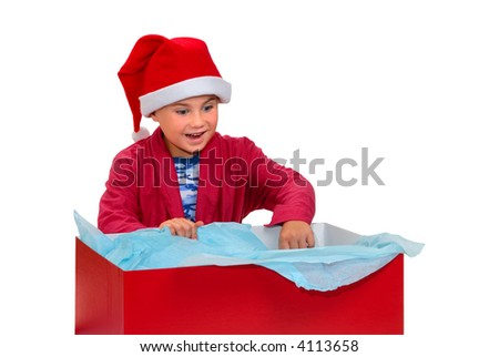 Young boy, in robe and Santa hat, opening a big red gift box, isolated on white with clipping path - stock photo