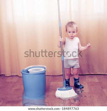 Young boy in rubber boots with mop. A lot of water on the flor - stock photo