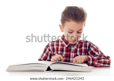 young boy in shirt reading from a big book - stock photo