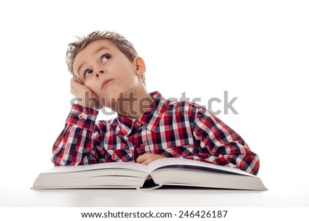 young boy in shirt with big book fantasizing - stock photo