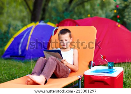 young boy in summer camp, relaxing with tablet - stock photo