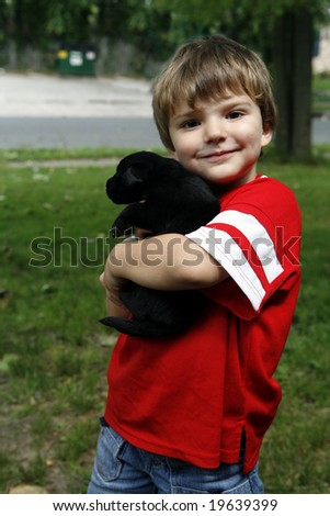 Young boy in the yard with his puppy. - stock photo