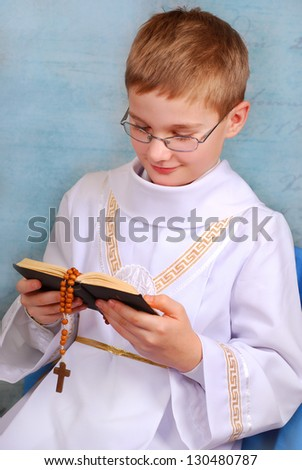 young boy in white alb going to the first holy communion and praying with prayer book - stock photo
