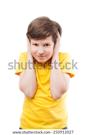 Young boy in yellow t-shirt shuts his ears by hands - stock photo