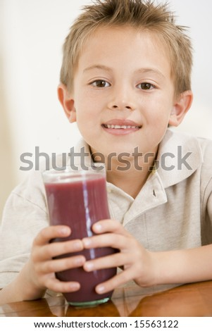 Young boy indoors drinking juice smiling - stock photo