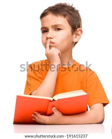 Young boy is daydreaming while reading book, isolated over white - stock photo