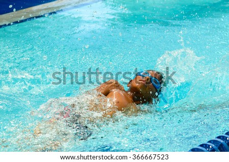Young boy is doing a competition in a private swimming pool. - stock photo