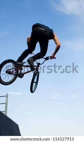 young  boy is jumping with his BMX Bike at the skate park - stock photo