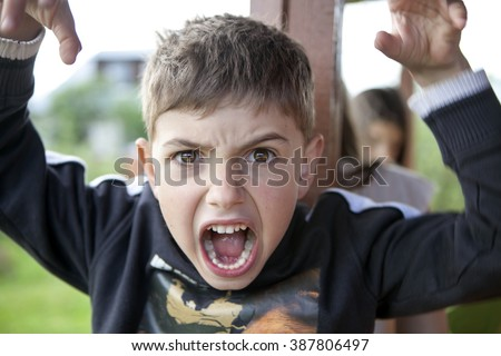 young boy is making face and gesturing with hands as if he is going to attack - stock photo