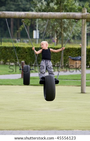 Young boy is playing at a park. - stock photo