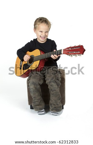 Young boy is playing on the guitar. - stock photo
