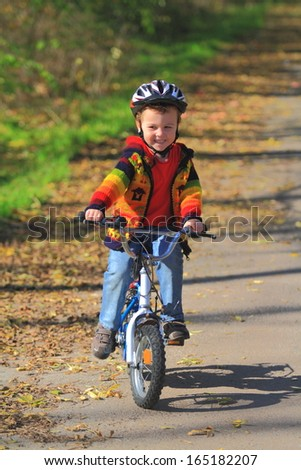 Young boy is riding his bike on autumn day - stock photo