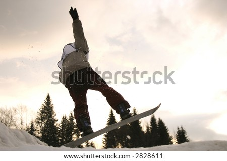 Young boy jumping high on a snowboard. - stock photo