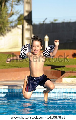 Young boy jumping in the pool - stock photo