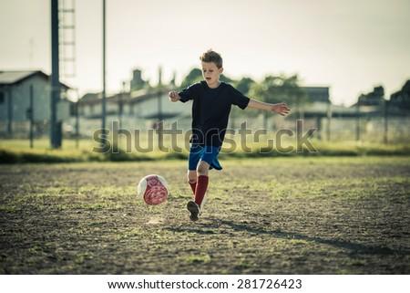 Young boy kicking ball - stock photo