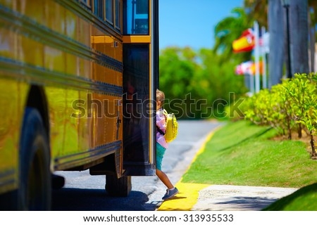 young boy, kid getting on the school bus, ready to go to school - stock photo