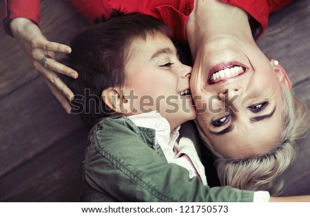 Young boy kissing her mum - stock photo
