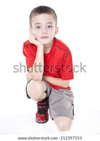 Young boy kneeling with hand supporting chin isolated on white background - stock photo