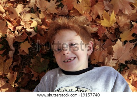 Young boy laying in gorgeous autumn leaves. - stock photo