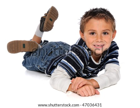 Young boy laying on floor over white background - stock photo
