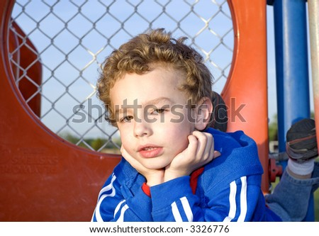 Young boy laying on playground equipment outdoors/outside - stock photo