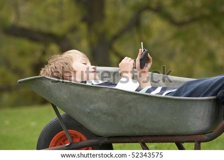 Young Boy Laying Wheelbarrow Using Smart Mobile Phone - stock photo