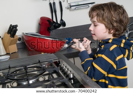 Young boy learning to cook in a modern kitchen - stock photo
