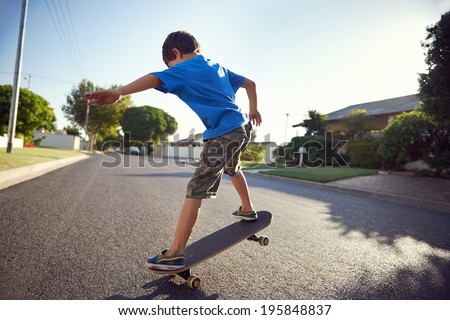 young boy learning to ride skateboard in the suburb street having fun. - stock photo
