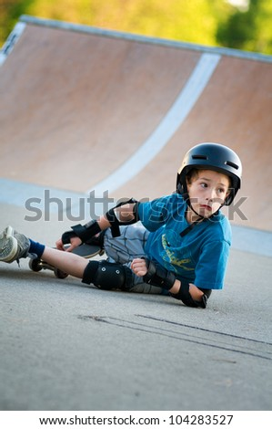 young boy learning to skateboard falls over - stock photo