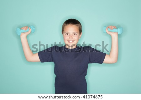 Young boy lifting small weights on blue background - stock photo