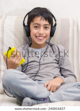 young boy listening music with smart phone and headphone - stock photo
