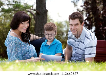 Young boy looking a digital tablet with parents in park - stock photo