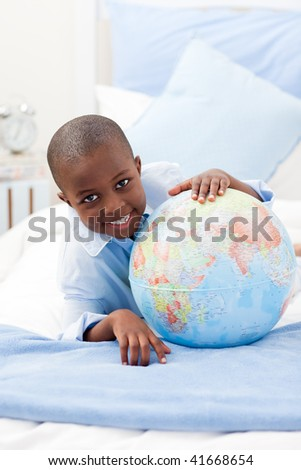 Young Boy looking at a globe while smiling at the camera - stock photo
