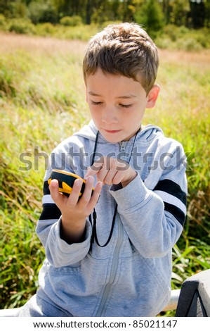 young boy looking at gps while geocaching - stock photo