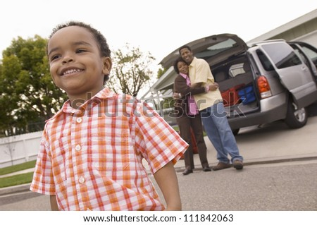 Young boy looking away with parents in background embracing each other - stock photo