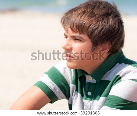 Young Boy Looking Out Into The Distant at The Beach - stock photo