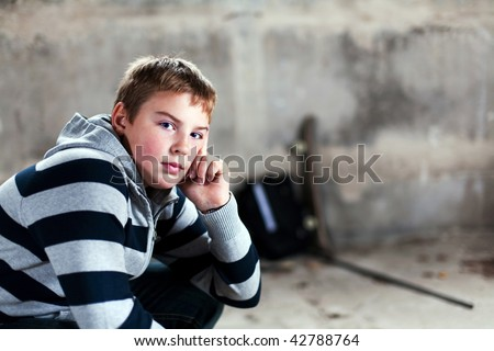 Young boy looking straight against grunge background flash lit 3 light sources - stock photo