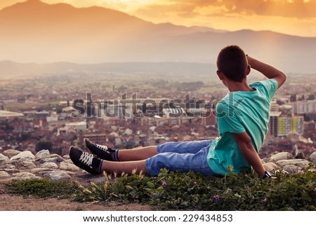 young boy looking to the city - stock photo