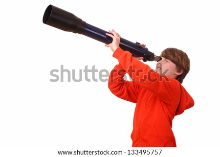 Young boy looks through a telescope on white background - stock photo