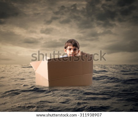Young boy lost in the middle of the sea - stock photo