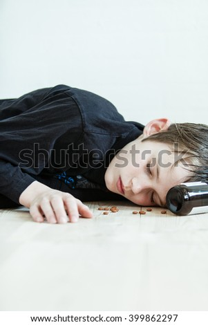 Young boy lying dead on the floor after committing suicide with a bottle of prescription drugs with tablets scattered around his face and the empty bottle at his head - stock photo