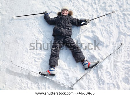 Young boy lying in cross-country skis and poles and stretching out arms and legs inside winter forest at sunny day - stock photo