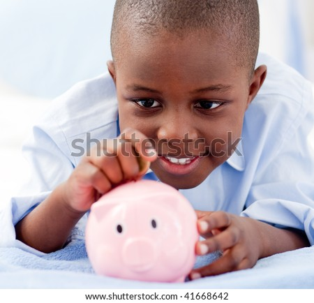 Young Boy lying on his bed putting money into a piggy bank - stock photo