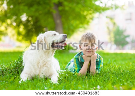 Young boy lying with golden retriever dog on green grass. - stock photo