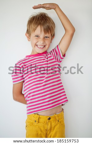 Young boy measuring his growth in height - stock photo