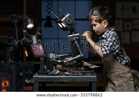 Young boy mechanic repairing the robot in the workshop at night - stock photo