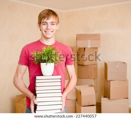 Young boy moving house to college, holding pile books and plant - stock photo