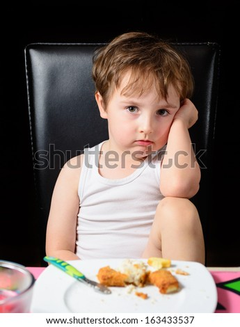 Young boy not happy being told to finish his meal - stock photo