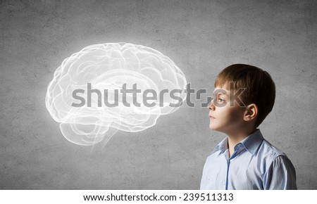Young boy of school age looking thoughtfully away - stock photo