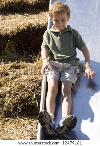 Young boy on playground slide with straw bales in background - stock photo